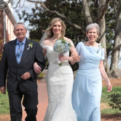 Bride being escorted down the aisle by her mother and her father at Forest Hill Church outside.