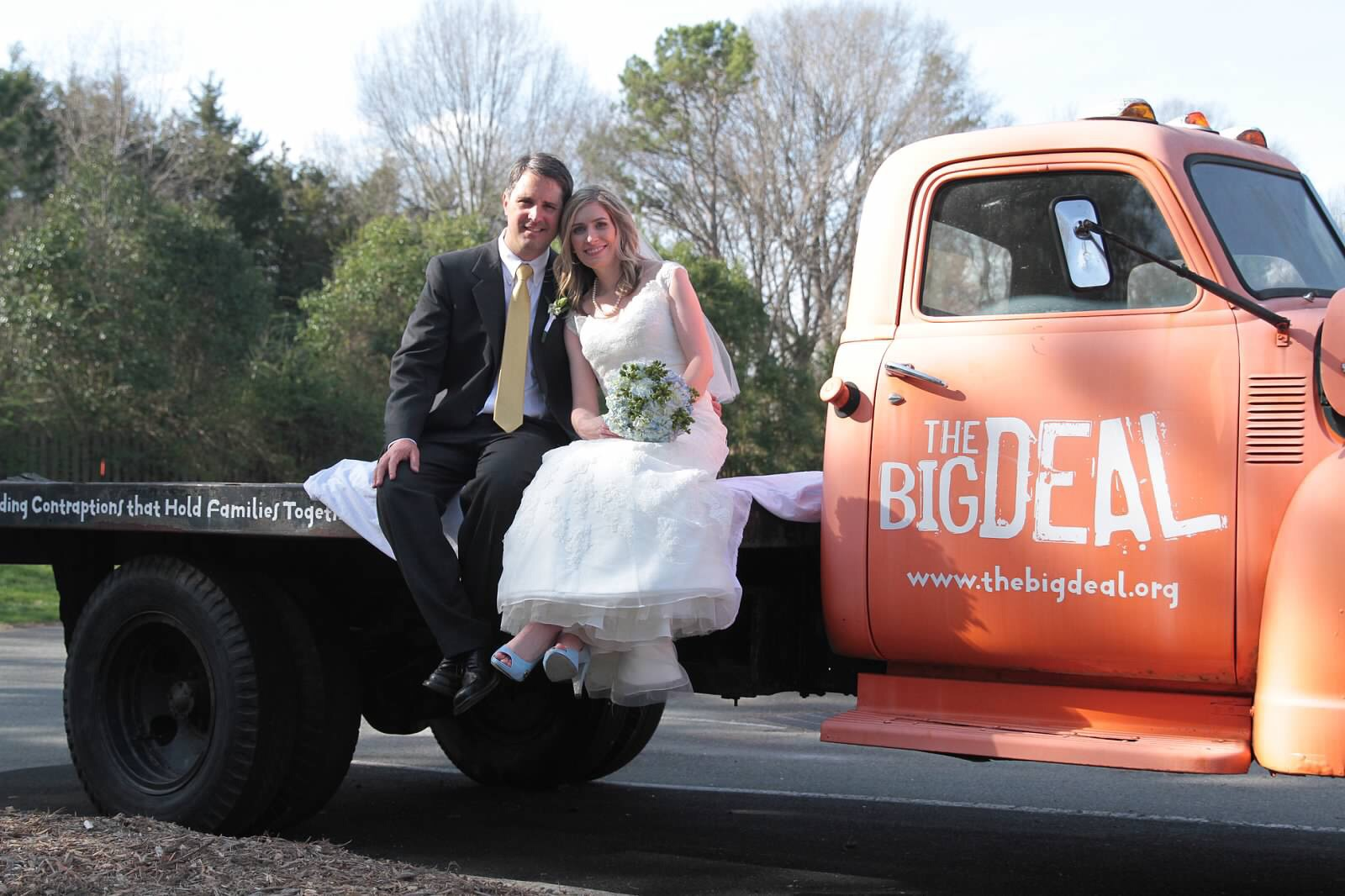 Bride and groom on a red truck for photos.
