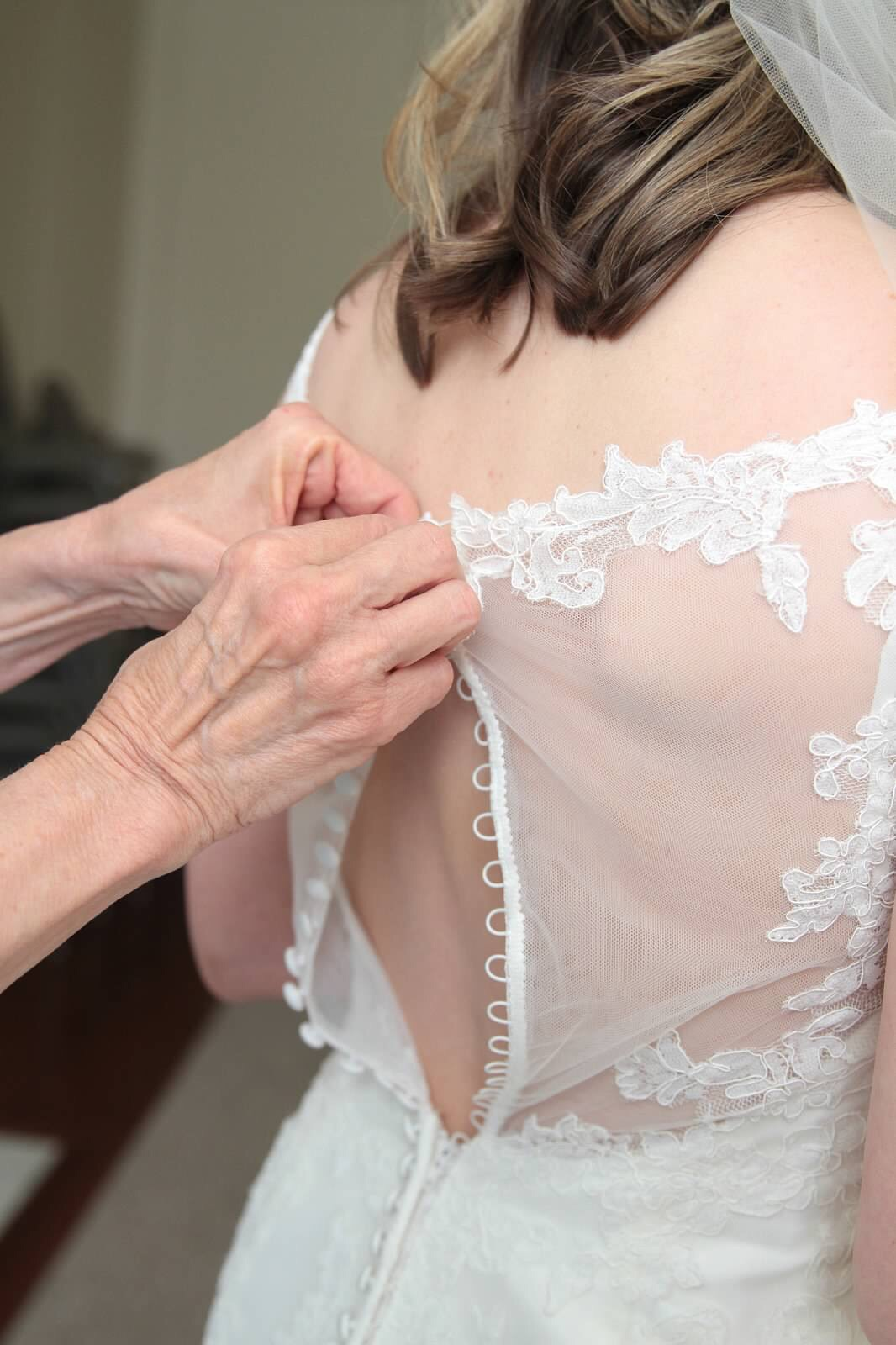 Bride's mother helping her button her dress up