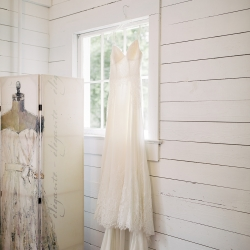 Bridal dress hangs delicately from a window during a summer wedding coordinated by Magnificent Moments Weddings