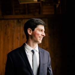 Groom smiles as he prepares for his wedding day at The Dairy Barn in Fort Mill, South Carolina