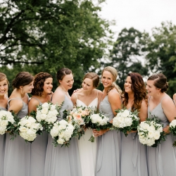 Bride and bridesmaids are all smiles as they pose for Cameron Faye Photography during their summer wedding at The Dairy barn