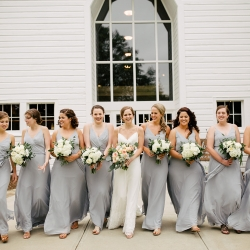 Bride poses with her bridesmaids all wearing soft gray the perfect color for a summer wedding captured by Cameron Faye Photography