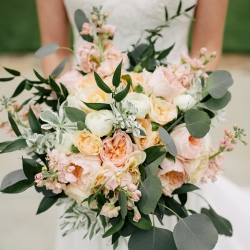 Bride holds a stunning bouquet created by Buy the Bunch featuring lush greens and soft pink flowers