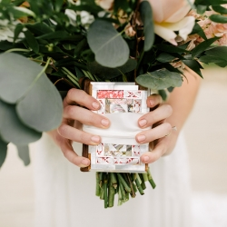 Bride shows off a special memento held during here wedding ceremony coordinated by Magnificent Moments Weddings