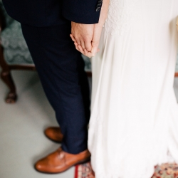 Bride and groom hold hands and read sweet love notes during their first look before walking down the aisle to their wedding ceremony planned by Magnificent Moments Weddings