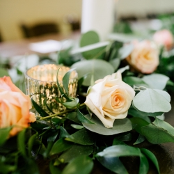 Stunning farm house table featured greenery garland, soft pink roses and white candles designed by Buy the Bunch