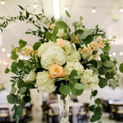 Stunning centerpieces feature lush greenery and white hydrangeas created by Buy the Bunch for a summer wedding