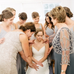 Bridesmaids and family pray over the bride as she prepares to walk down the aisle to her ceremony at The Dairy Barn