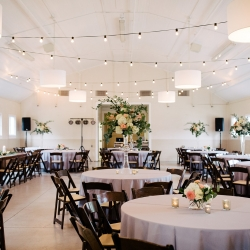 Gray linens and dark chairs from creative solutions served as the perfect setting for guests at a Dairy Barn Wedding