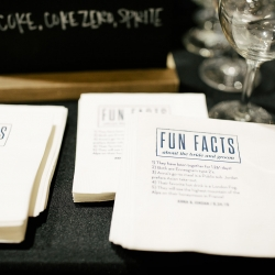 Custom bar napkins revealed fun facts about the bride and groom made a fun touch for a summer wedding at The Dairy Barn