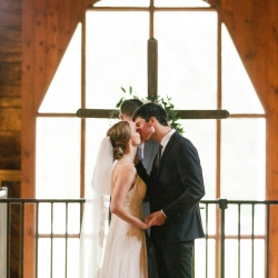 Bride and groom exchange a kiss after their vows during a wedding ceremony at The Dairy Barn planned and coordinated by Magnificent Moments Weddings
