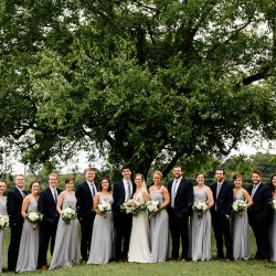 Bride and groom pose with their bridal party under a large oak tree all captured by Cameron Faye Photography