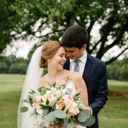 Bride holds a stunning bouquet created by Buy the Bunch while laughing with her husband during their Dairy Barn wedding