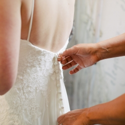 Bride gets her dress zipped as she prepares to walk down the aisle during her ceremony planned by Magnificent Moments Weddings