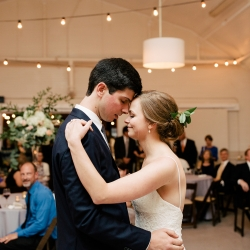 Bride and groom share a first dance during their summer wedding reception coordinated by Magnificent Moments Weddings