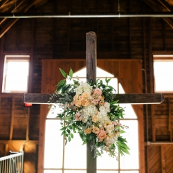 Buy the Bunch creates a stunning floral accent to a wooden cross that served as the backdrop for a summer ceremony at The Dairy Barn