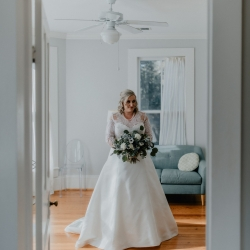 Bride holds a stunning bouquet featuring dark blue blooms and white accents created by Heatherly Event and Floral Design