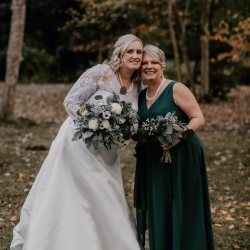 Bride poses with her bridesmaid during her fall wedding coordinated by Magnificent Moments Weddings