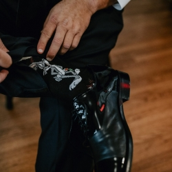 Candle and Quill Photography captures the fun socks of a groom as he prepares for his fall wedding at Ritchie Hill