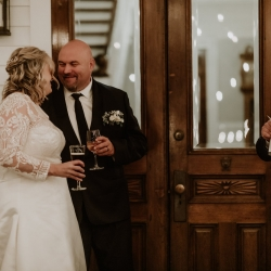 Bride and groom smile as their family raises a toast all captured by Candle and Quill Photography