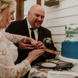 Bride and groom cut their cake from Wentworth and Fenn during their wedding reception coordinated by Magnificent Moments Weddings