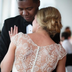 Bride and groom first dance with her head laying on his shoulder and a gorgeous lace back dress.