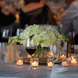 Hydrangea centerpiece at the Mint Museum Uptown with gold table numbers and votive candles.