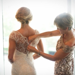 Mother of the bride buttoning up her daughter's bridal gown.