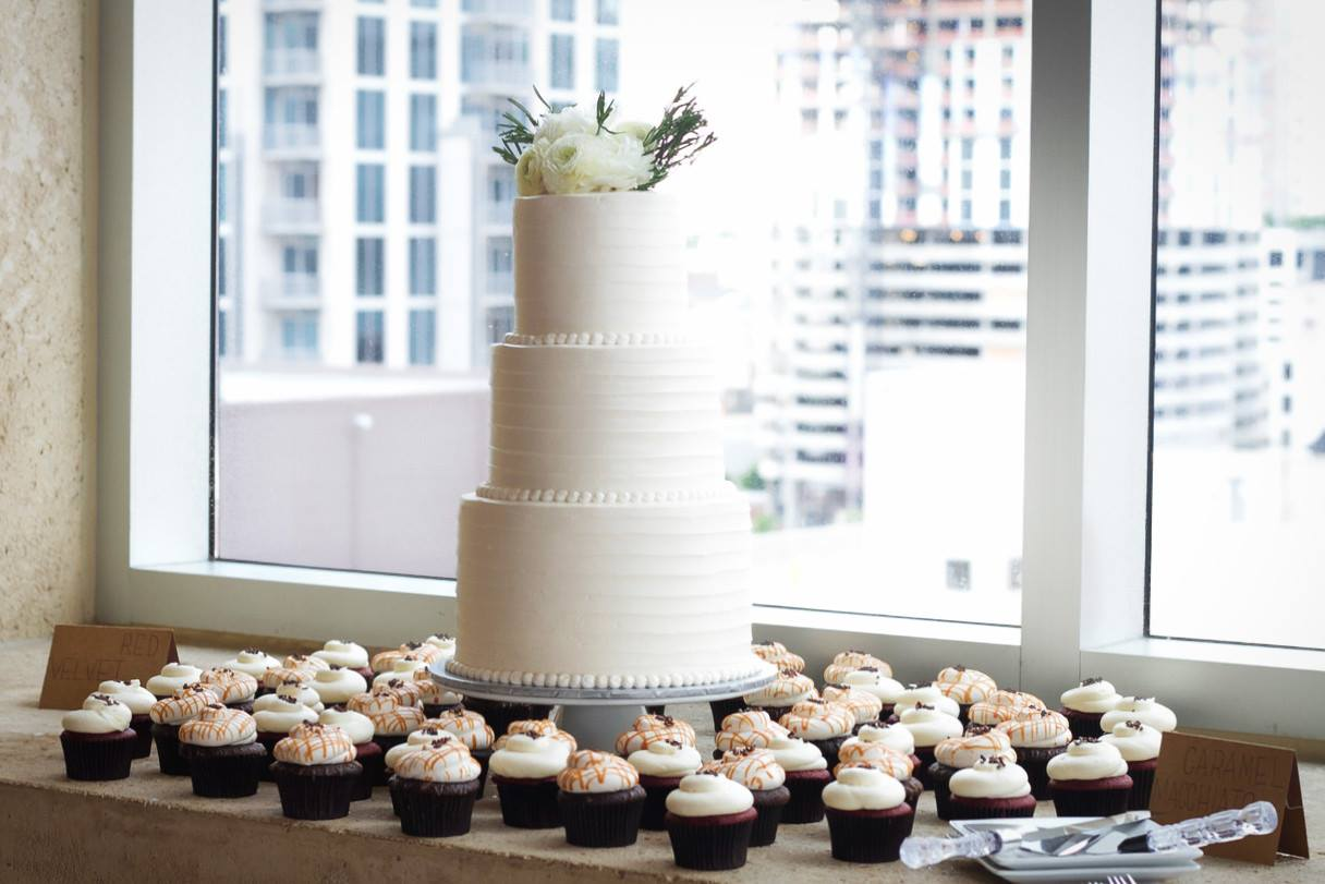 Suarez bakery cake and cupcakes for a wedding with flowers as a topper.