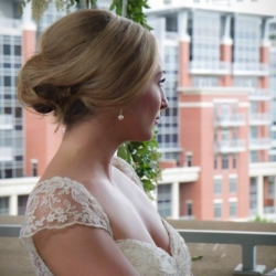 Beautiful blonde bride with an updo and a lace dress getting married on the balcony at the Mint Museum Uptown.