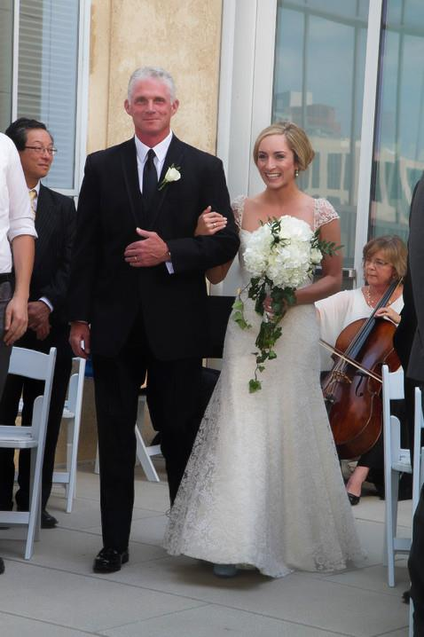 Bride walking down the aisle being escorted by her father at the balcony on the Mint Museum.