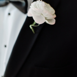 white ranunculus boutonniere on a Magnificent Moments Weddings groom