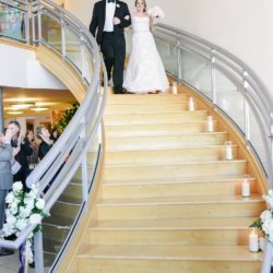 Bride and groom walking down the staircase at Levine Museum of the New South