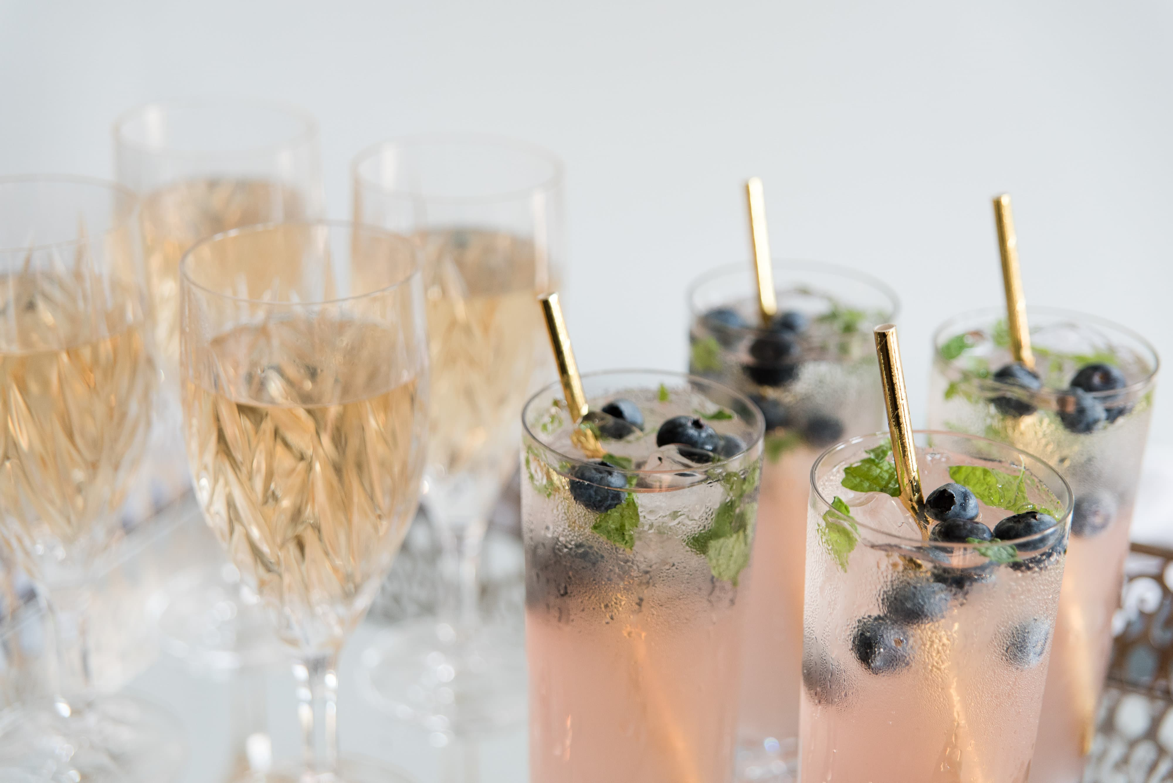 Signature wedding cocktails with gold straws and fresh blueberries accent a French Blue Styled Shoot designed by Magnificent Moments Weddings