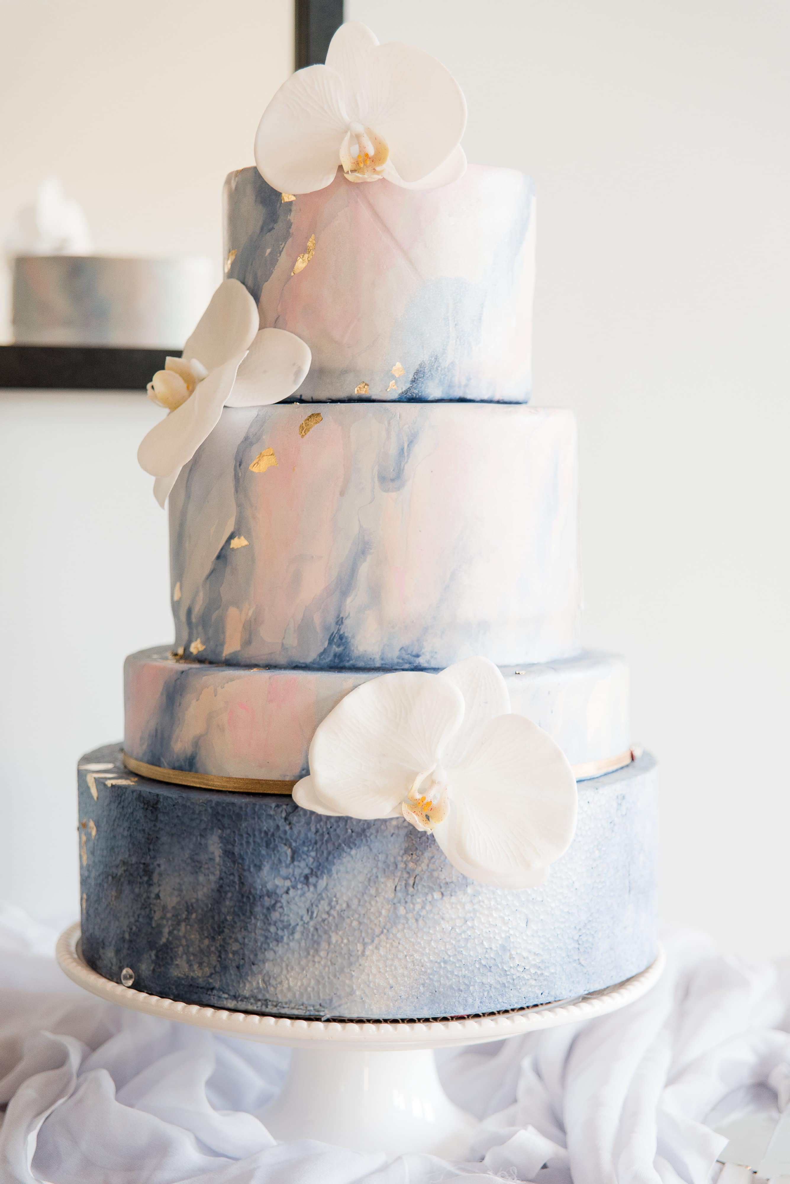 Four tier classic wedding cake with blue marbled details and gold flakes accented by large white orchids created by Sky's the Limit Bridal Sweets