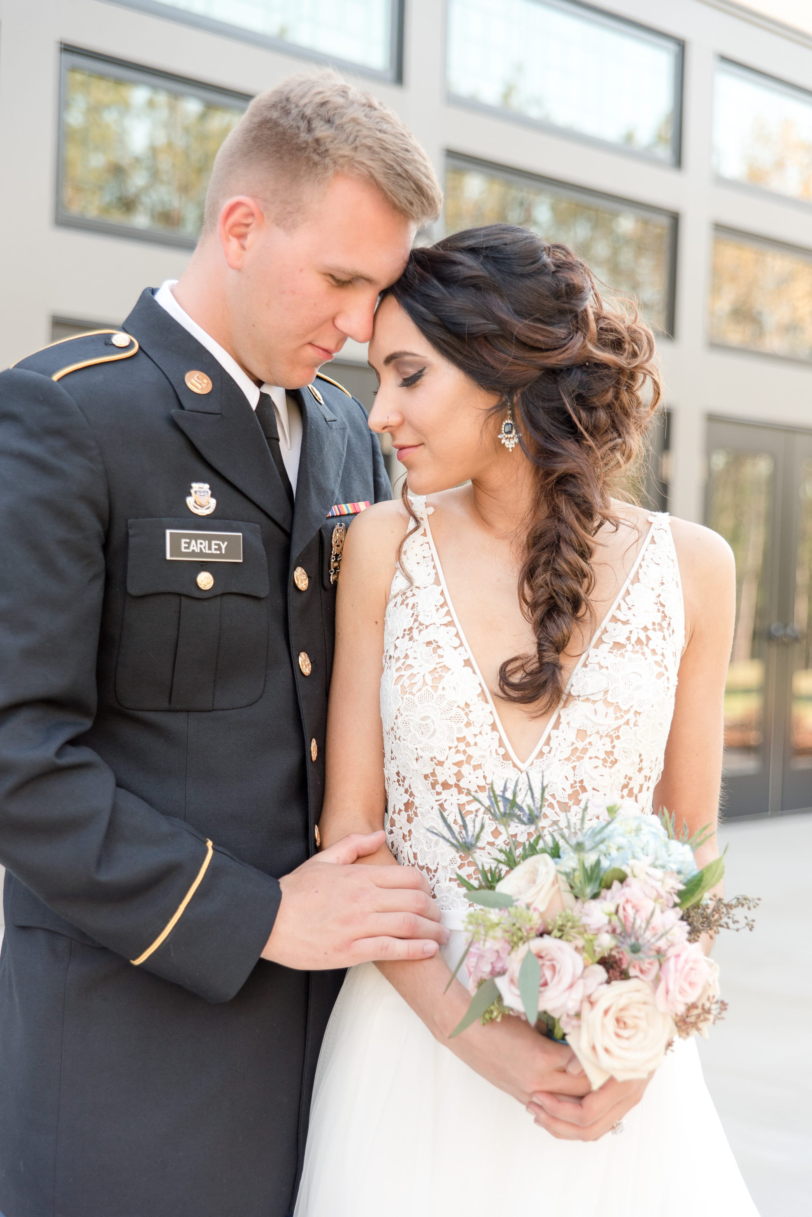 Groom embraces bride who holds a stunning bridal bouquet designed by Magnificent Moments Weddings