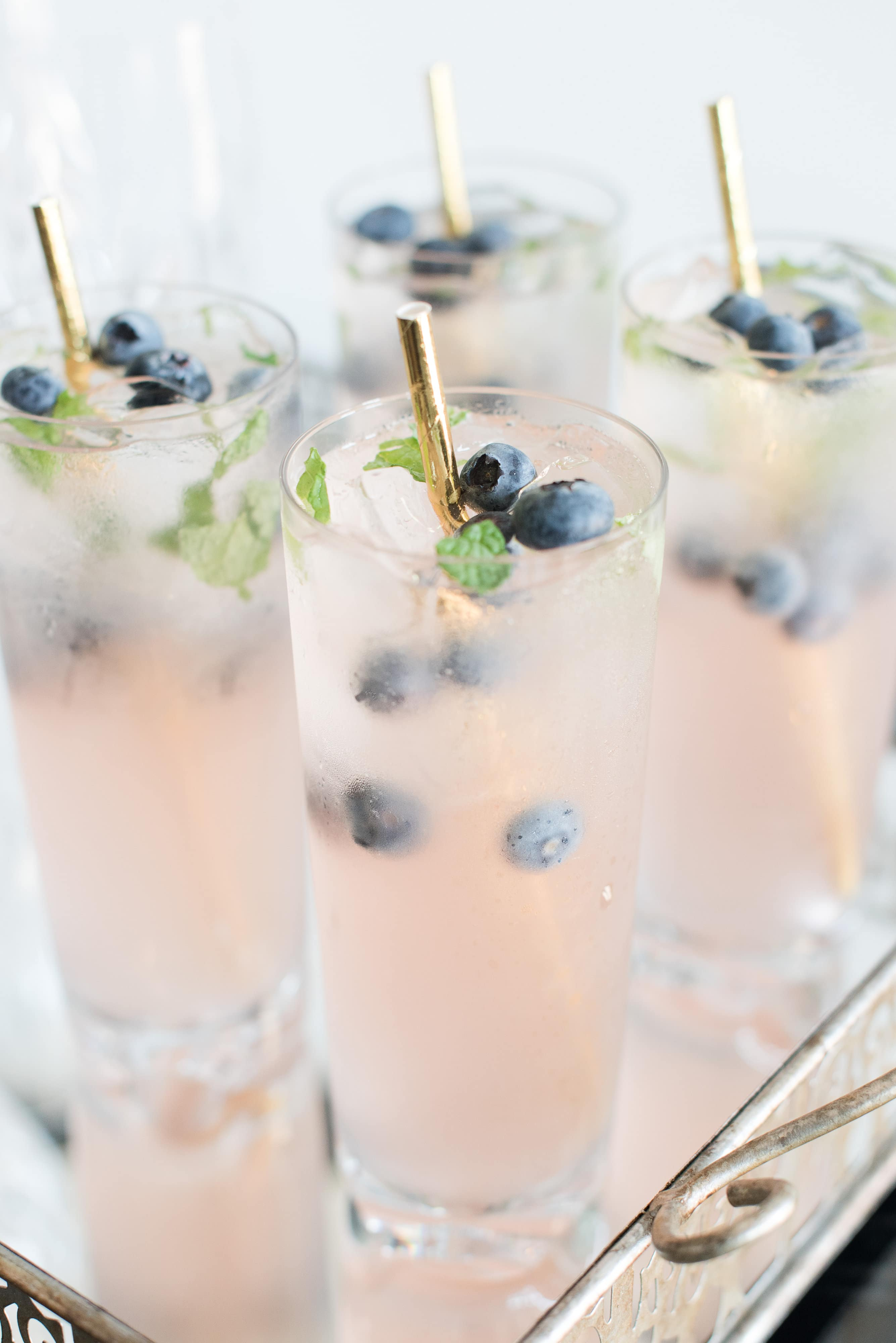 Signature cocktails with gold straws and fresh blueberries accent a French Blue Styled Shoot captured by Charlotte Wedding Collective