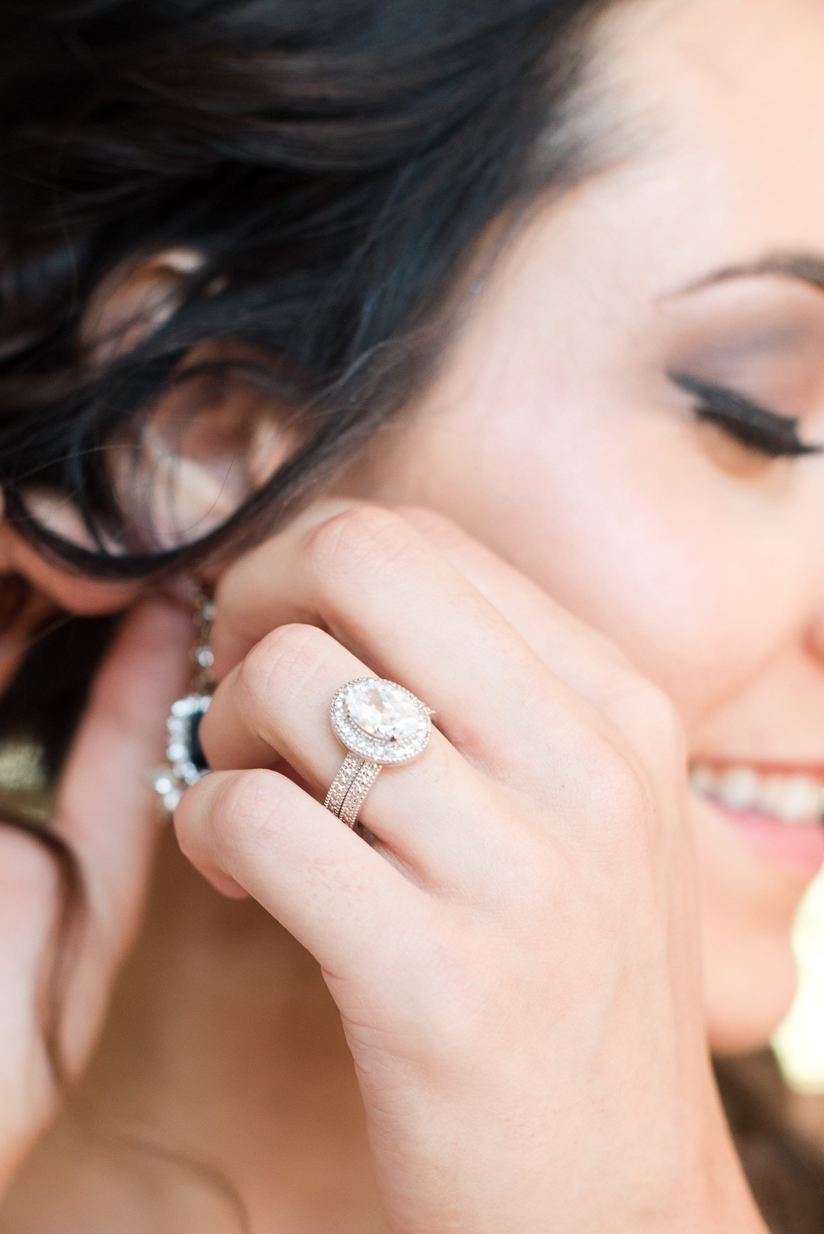 Bride puts on earring and shows of amazing makeup by Jennifer Carver