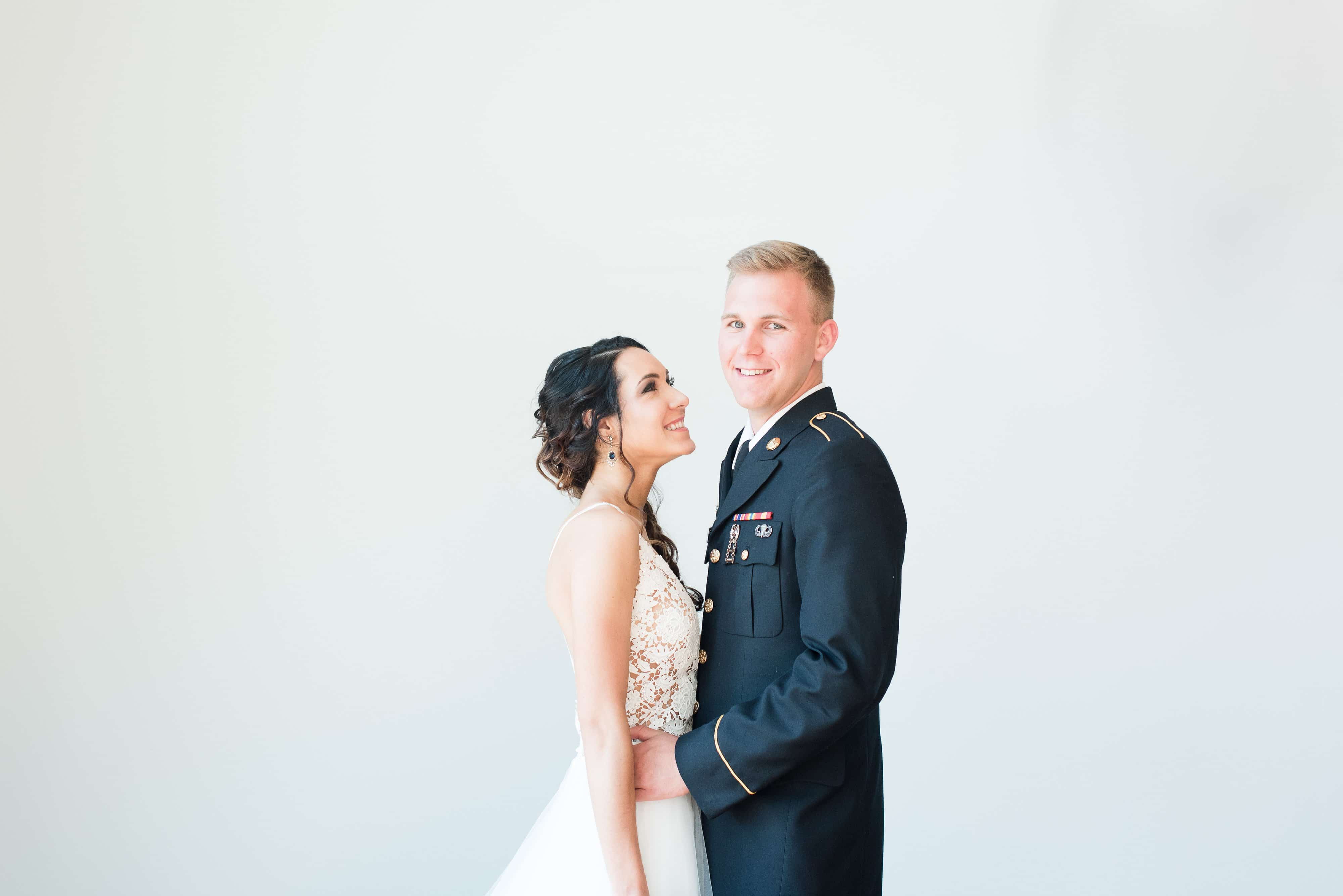 Bride stands with groom with beautiful hair by Michelle Seusss