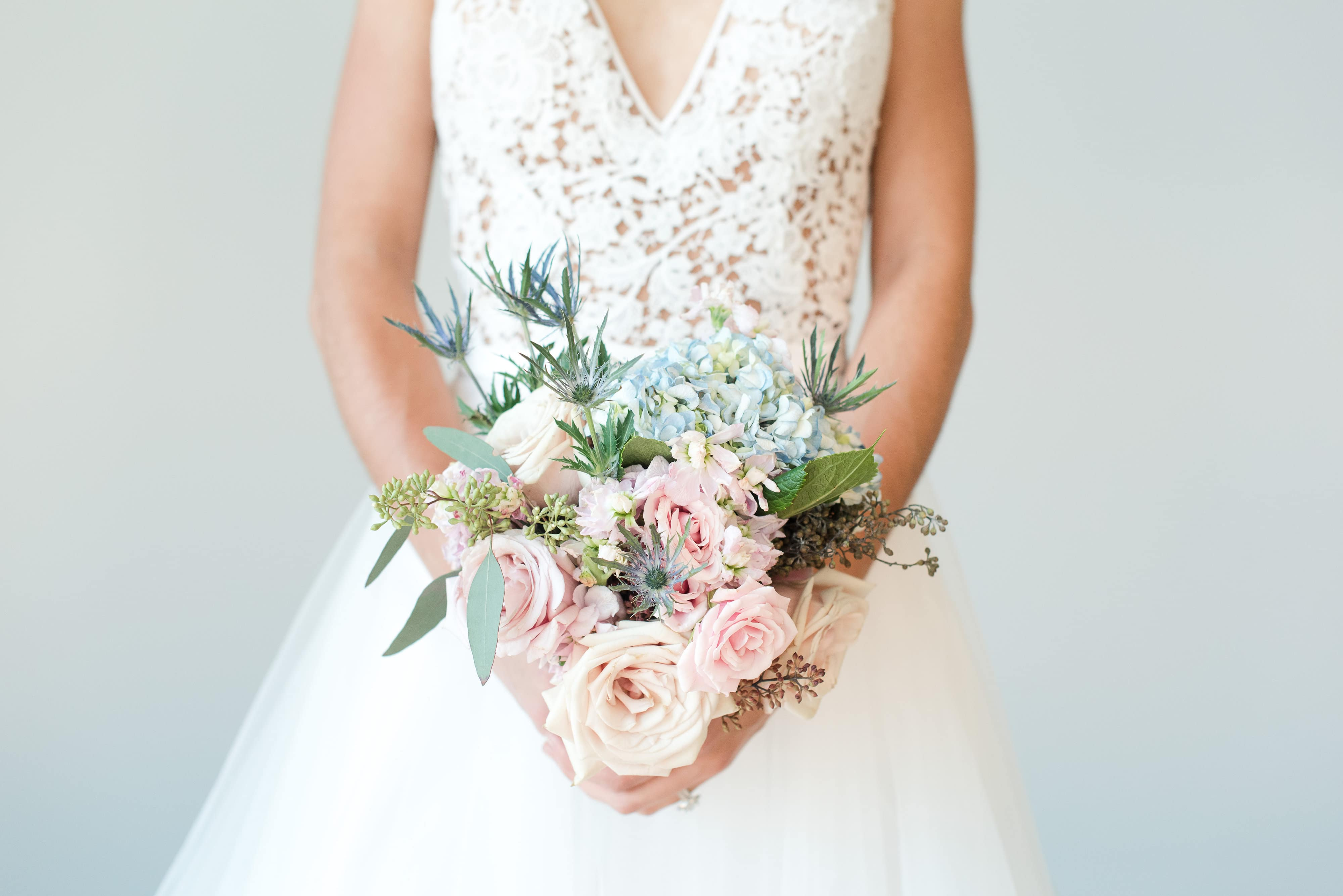 Bride holds bridal bouquet with pink roses and blue hydrangeas created by Magnificent Moments Weddings