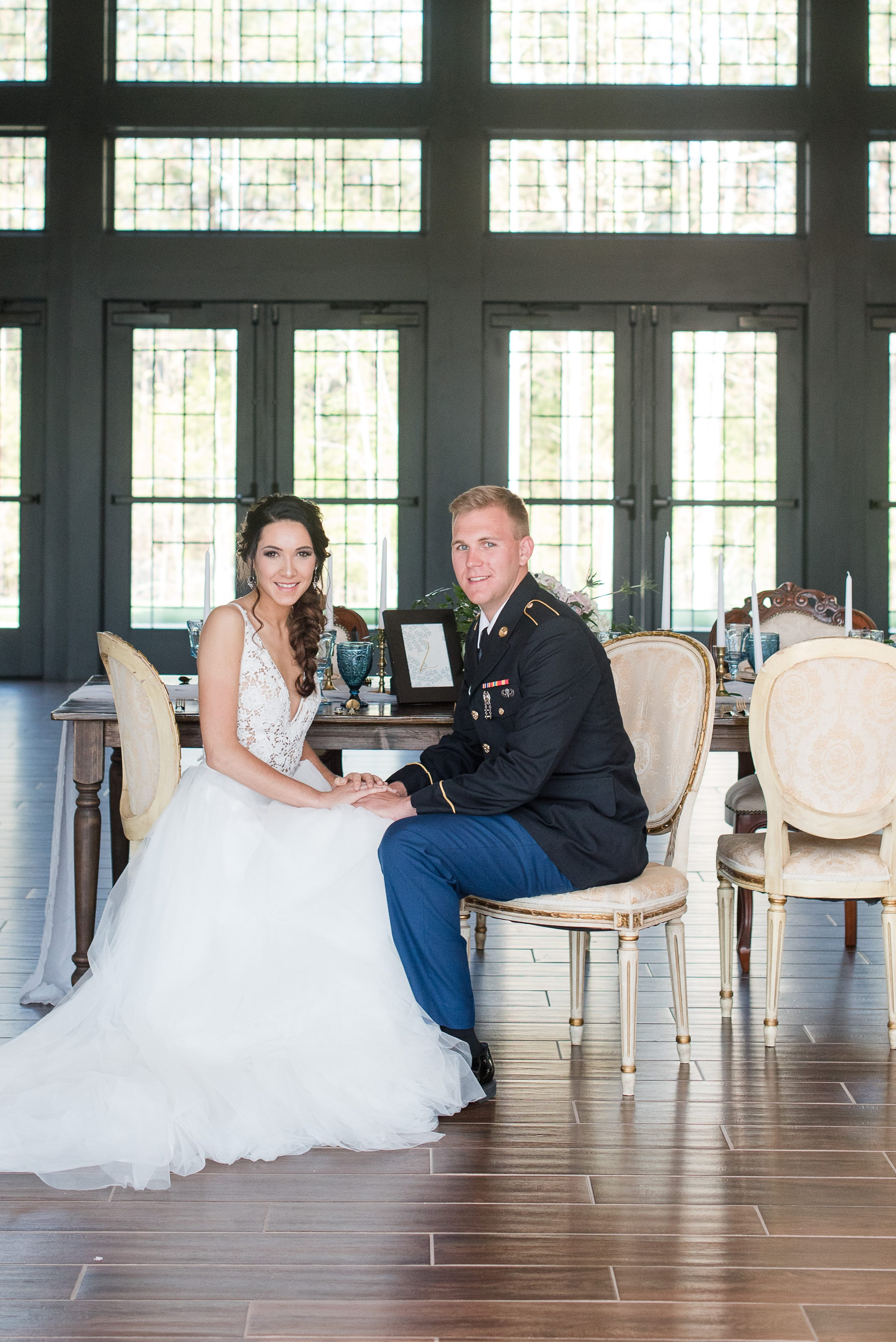 Bride and groom sit on vintage white chairs rented from Evermore Events