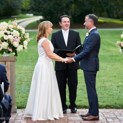 Bride and groom exchange vows amid stunning floral pieces created by What's Up Buttercup