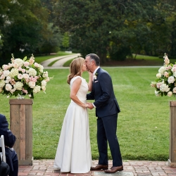 Bride and groom share a kiss sealing their vows during their wedding at The Mint Museum Randolph coordinated by Magnificent Moments Weddings
