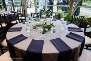 Crisp white linens and deep blue napkins create a stunning tablescape for a wedding at The Mint Museum Randolph