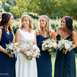 Bride poses with her bridesmaids wearing dark navy and holding beautiful bouquets created by What's Up Buttercup