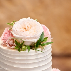 Soft pink flowers served as the stunning cake topper for a wedding coordinated by Magnificent Moments Weddings