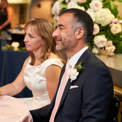 Bride and groom listen as loved ones and friends toast them during their wedding reception coordinated by Magnificent Moments Weddings