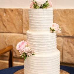 Stunning three tiered cake featured white frosting and and simple floral accents for a wedding at The Mint Museum Randolph