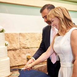 Bride and groom cut their cake during their wedding reception at The Mint Museum Randolph coordinated by Magnificent Moments Weddings
